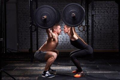 Sticker Barre de levage Crossfit par femme et homme en séance d'entraînement en groupe contre mur de briques.