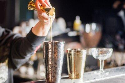 Sticker bartender is preparing a cocktail. Bartender pours a cocktail
