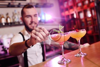 Sticker beau barman prépare un cocktail alcoolisé orange et sourit sur le fond d'un bar ou d'une boîte de nuit