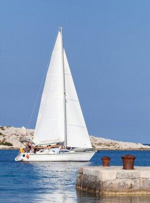 Sticker Bluré yacht à voile sur son chemin hors du port est en passant par les deux bornes en foyer