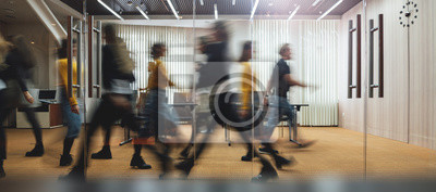 Sticker Businesspeople walking at modern office. Group of business employees at coworking center. Motion blur. Concept work process. Wide image