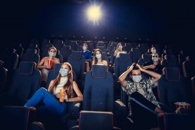 Sticker Cinema, movie theatre during quarantine. Coronavirus pandemic safety rules, social distance during movie watching. Men and women wearing protective face mask sitting in a rows of auditorium, eating