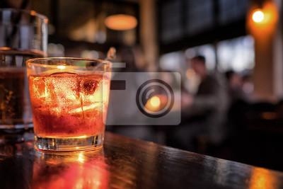 Sticker Cocktail en gros plan dans un bar. Des personnes floue en arrière-plan. Mise au point sélective sur la boisson glacée et le verre.