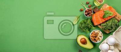 Sticker Concept de régime Keto - saumon, avocat, œufs, noix et graines, fond vert clair, vue de dessus