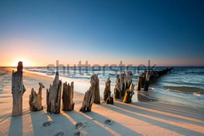 Sticker Coucher de soleil sur la plage de la mer Baltique et le vieux brise-lames en bois