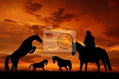 cowboy Silhouette avec des chevaux dans le coucher du soleil