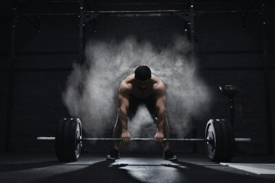 Sticker Crossfit athlete preparing to lift heavy barbell in a cloud of dust at the gym. Barbell magnesia protection.