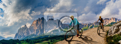 Sticker Cycling woman and man riding on bikes in Dolomites mountains andscape. Couple cycling MTB enduro trail track. Outdoor sport activity.