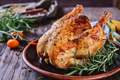 Sticker Delicious, freshly baked, crispy, baked chicken is appetizing served on a ceramic dish next to a sprig of fragrant rosemary