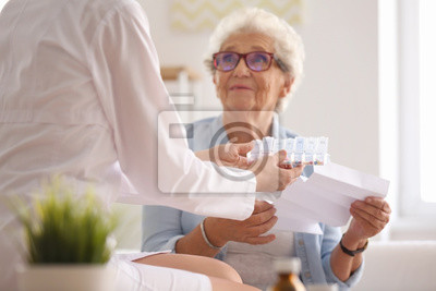 Sticker Doctor giving medicine and instruction to senior woman at home