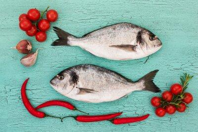 Sticker Dorado frais poisson avec des légumes sur la table bleue. Copier l'espace, vue de dessus
