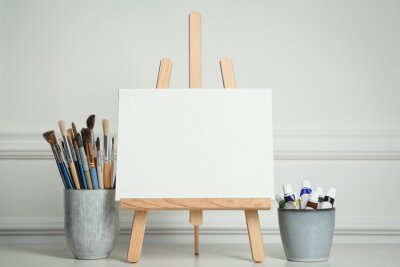 Sticker Easel with blank canvas, paints and brushes on white wooden table