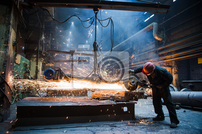 Sticker Employee grinding steel with sparks - focus on grinder. Steel factory.