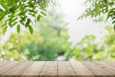 Sticker Empty wood table top and blurred green tree in the park garden background - can used for display or montage your products.