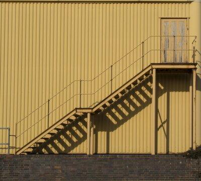 Sticker Escalier menant à travers une paroi latérale métallique.