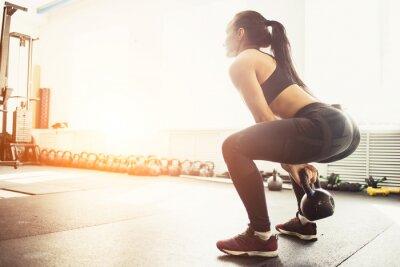 Sticker Femme athlétique exerçant avec une cloche de bouilloire en position accroupie. Femme musculaire faisant des exercices de crossfit à la gym.