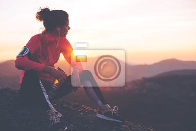 Sticker Femme athlétique reposant après un dur entraînement dans les montagnes au coucher du soleil. Vêtements sportifs.