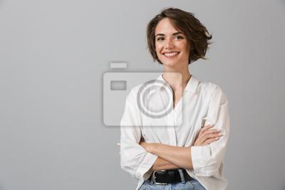 Sticker Femme d'affaires de jeunes heureux posant isolé sur fond de mur gris.
