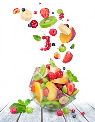Sticker fruit salad in glass bowl with ingredients in the air on white w