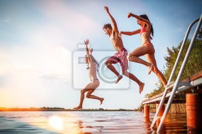 Sticker Groupe d'amis sautant dans le lac depuis la jetée en bois. S'amuser le jour d'été.
