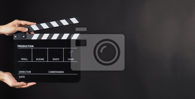 Sticker Hand is holding Black clap board or movie slate  use in video production , movie ,film, cinema industry on black background.It have write in number.