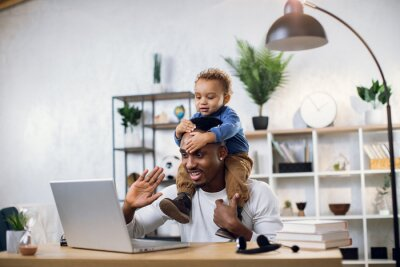 Sticker Handsome male freelancer smiling and waving during video chat on modern laptop. Young afro american father working from home and taking care of his little son.