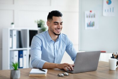 Sticker Handsome young Arab businessman working with laptop computer at his desk in office
