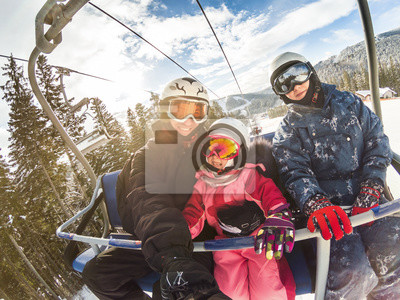 Sticker happy smiling family skiers on ski lift making selfie