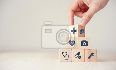 Sticker Health Insurance Concept, Hand arranging wood cube stacking with icon healthcare medical on wood background, copy space, financial concept.