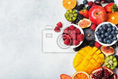 Sticker Healthy raw rainbow fruits, mango papaya strawberries oranges passion fruits berries on oval serving plate on light kitchen top, top view, copy space, selective focus
