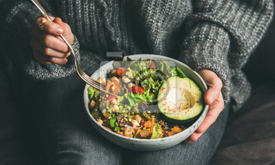 Sticker Healthy vegetarian dinner. Woman in jeans and warm sweater holding bowl with fresh salad, avocado, grains, beans, roasted vegetables, close-up. Superfood, clean eating, vegan, dieting food concept