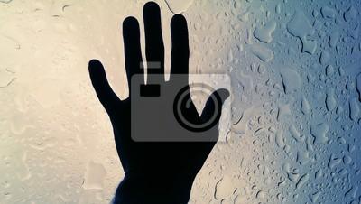Homme de main sur un verre humide