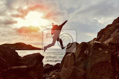 Sticker Homme sautant randonneur sur un espace entre deux rochers