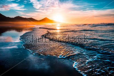 Sticker Incroyable coucher de soleil sur la plage avec un horizon sans fin et des silhouettes au sol, et des vagues incroyablement mousseuses. Collines volcaniques en arrière-plan.