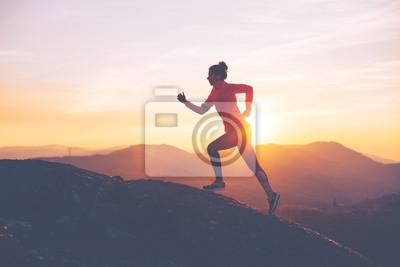 Sticker La fille athlétique finit une course dans les montagnes au coucher du soleil. Vêtements sportifs. Flou de mouvement intentionnel.