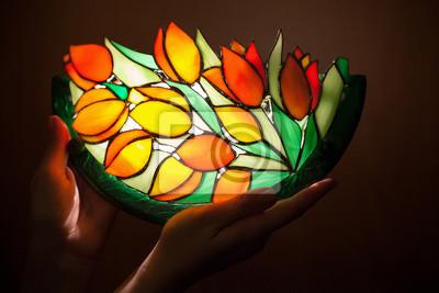 Lampe en verre teinté à la main avec des fleurs de tulipes dans les mains de la femme