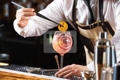 Sticker Le barman élégant fabrique un cocktail rose contenant des copeaux d'orange dans l'arrière-plan du bar.