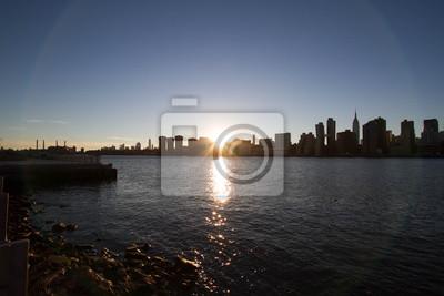 Le coucher de soleil derrière Manhattan réfléchit sur East River