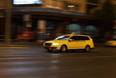 Sticker le taxi jaune se déplace dans la rue la nuit de la ville