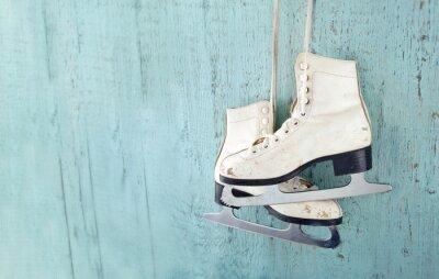 Sticker Les patins de glace de la femme suspendue sur fond de bois bleu