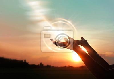 Sticker Mains de femme priant pour la bénédiction de Dieu sur fond de coucher de soleil