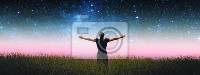 Sticker Man with arms wide open standing on the grass field against the night starry sky. Elements of this image furnished by NASA.