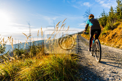 Sticker Mountain biking woman riding on bike in summer mountains forest landscape. Woman cycling MTB flow trail track. Outdoor sport activity.