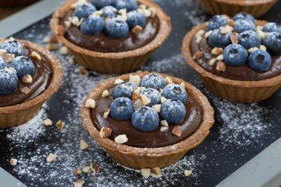 Sticker mousse au chocolat avec des bleuets frais et les noix dans tartelettes
