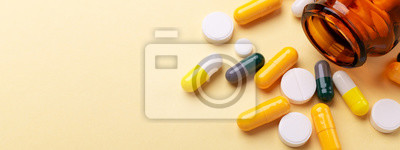 Sticker Multicolor tablets and pills capsules from glass bottle on yellow background Health care Close-up Horizontal banner Copy space