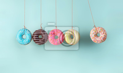 Sticker Newton's cradle from doughnuts. Collision balls made from donuts. Harm of sugar, donuts time or healthy diet concept. Dependence on flavoring, diabetes problems, weight loss.