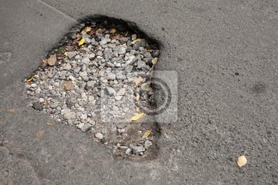Nid de poule avec du gravier sur endommagé route goudronnée urbain