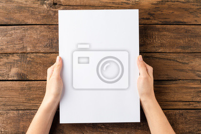 Sticker Overhead shot of woman's hands holding blank paper sheet on rustic wooden table. Close up