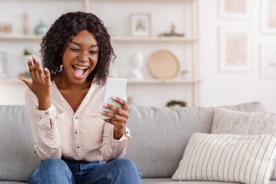 Sticker Overjoyed black girl celebrating success with smartphone at home, received good news