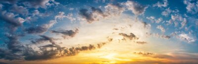 Sticker Panorama of dramatic sky with clouds at yellow-orange sunset.